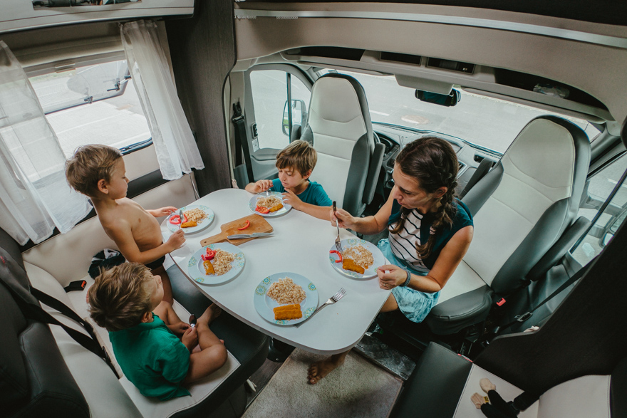 Mama sși cei trei băieți mănâncă prânzul în autorulota camper