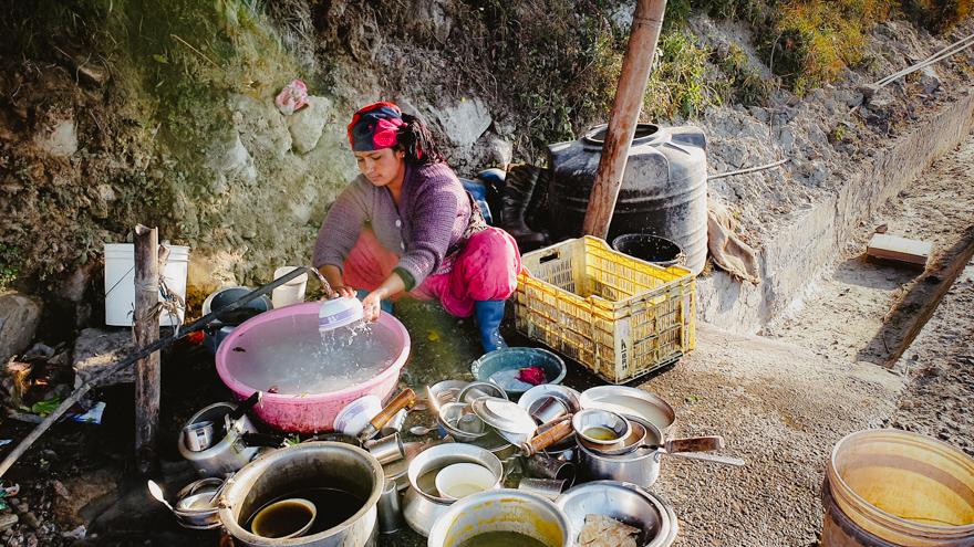 Femeie care spala vasele pe marginea strazii in Nepal