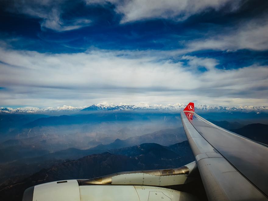 Avion deasupra norilor cu Himalaya in departare